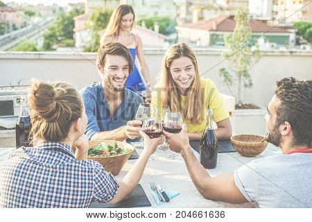 Cheerful friends cheering with red wine at rooftop barbecue party - Happy people doing bbq dinner outdoor with city view in background - Focus on bottom glasses - Food fun and friendship concept