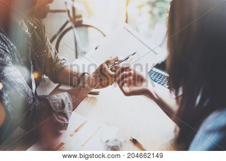 Coworkers working together in modern office.Bearded man talking with colleague and showing paper documents.Business people brainstorming concept.Horizontal.Blurred background.Flares.