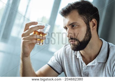 Unhealthy lifestyle. Cheerless addicted bearded man holding a glass with whisky and intending to drink it while being alone