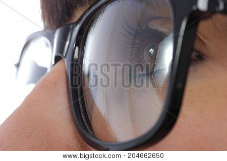 close-up of a young woman eye with black glasses