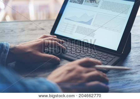 View of male hands typing on electronic tablet keyboard-dock station. Business information on device screen. Man working at office.Horizontal