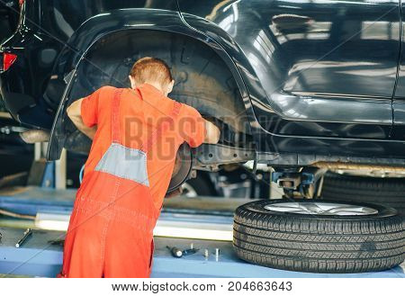 Mechanic inspecting a lifted car. Close - up