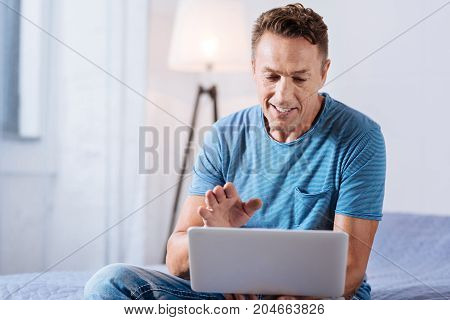 Hello there. Cheerful middle-aged man sitting on the bed in the bedroom and making a video call, using his laptop, while talking with his colleague