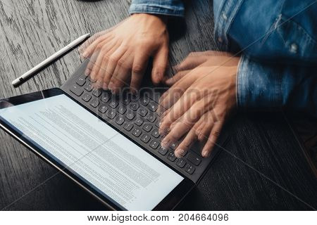 Closeup view of male hands fast typing on electronic tablet keyboard-dock station. Business information on device screen. Man working at office.Horizontal, top view