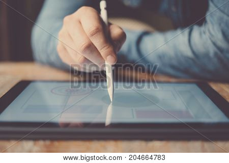 Man working contemporary electronic tablet while sitting at the wooden table at office.Men using digital stylus for pointing on center device screen.Blurred background. Horizontal closeup, front view