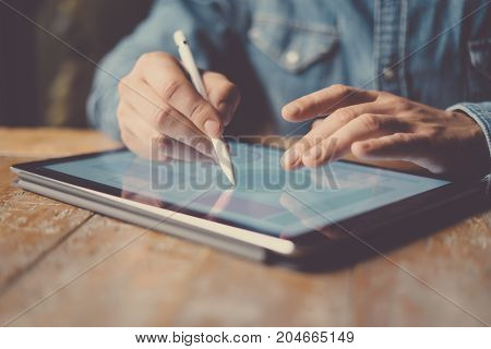 Man working contemporary electronic tablet while sitting at the wooden table at office.Men using digital stylus for drawning device screen.Blurred background. Horizontal