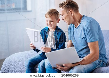 Careful reading. Cheerful little boy sitting on the bed next to his father and carefully reading the printouts in his hands while his father peeking at them as well