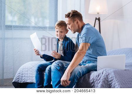 Getting ready for school. Pleasant little boy sitting on the bed with his father and reading the information from the printouts while doing his home assignment
