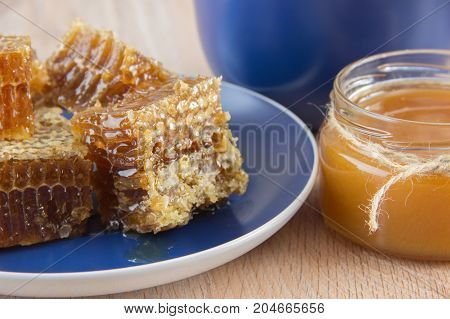 Pieces of golden honey comb on a table with tea lemon and cinnamon