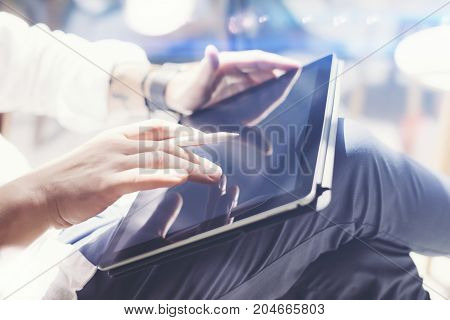 Businessman holding tablet on hand and working at office.Touching tablet screen.Blurred background.Horizontal
