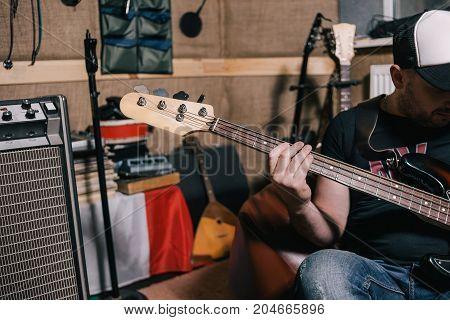 Bass guitar riff in music studio closeup. Unrecognizable male guitarist, messy musical garage, repetition before concert