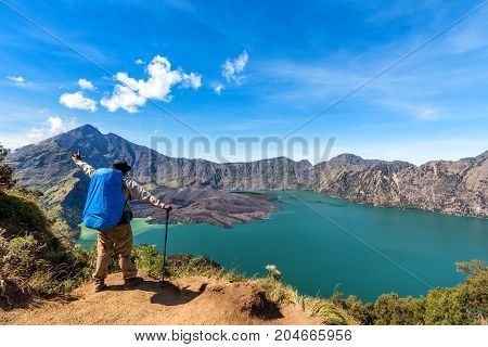 Hiker man with backpack spreading hand enjoy and happy with active volcano Baru Jari Lake Segara Anak and summit of Rinjani mountain view after finished climbing at Rinjani mountain Lombok Indonesia.
