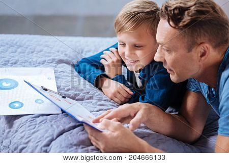 Immersed in reading. Pleasant little boy lying on the bed with his father and carefully looking at the charts on the printouts, studying them carefully