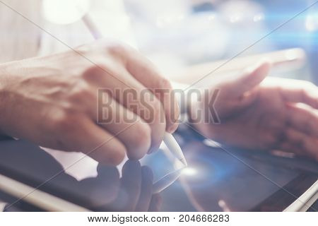 Closeup view of man holding digital tablet on hand and using electronic pen while working at sunny office.Pointing tablet screen.Blurred background.Horizontal.Visual effects