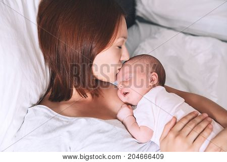 Mother kissing her newborn baby. Sleeping baby in the hands of his loving mother. Image of happy maternity and co-sleeping. Mom and child's first month of life at home.