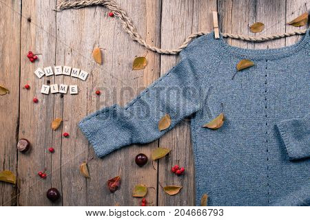 Autumn fall flat lay, top view. Warm knitted sweater, Fall Leaves, chestnuts, rowan berry and pumpkin with scrabble  inscription