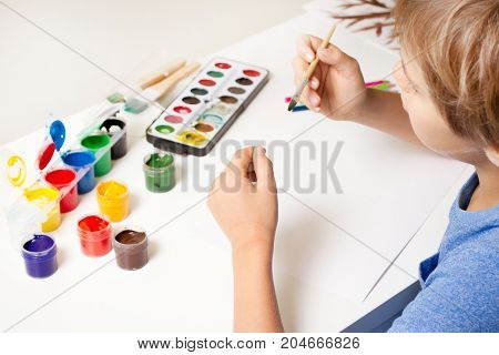 Boy painting with paintbrush and colorful gouache and watercolor paints