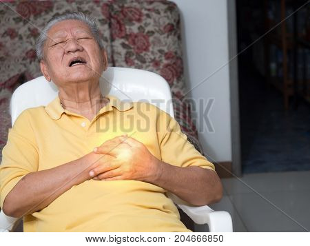 senile asian men sitting on a chair at living room with heart attacks.Both old man's hands on breast because of hard breathing Face old man with pain caused by heart disease.