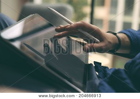 Close up view of businessman hand using stylus pen for touching the digital tablet screen. Blurred background. Horizontal
