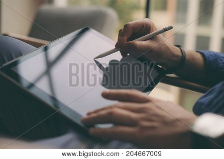 Close up view of male hands holding stylus pen and working on a digital tablet. Blurred background. Horizontal