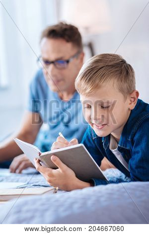 Sharing feelings. The focus being on the pleasant little boy lying on the bed and writing in his diary while his father lying behind him in the background