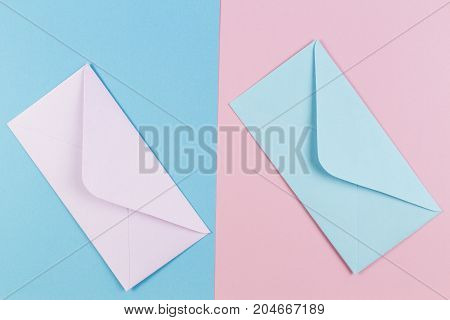 Pink and blue envelopes on colored pink and blue background. Top view