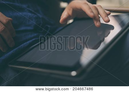Close-up view of male hands touching digital tablet screen. Blurred background. Horizontal