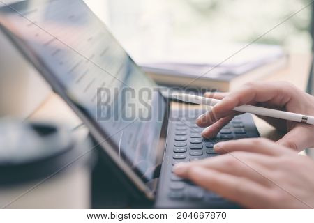 Closeup view of male hands typing electronic tablet keyboard-dock station.Blogger using mobile touchpad for work.Horizontal, blurred background