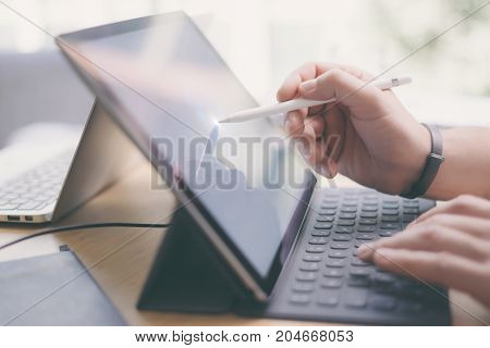Blogger using mobile touchpad for work.Closeup view of male hands using stylus pen for touching electronic tablet screen.Horizontal, blurred background