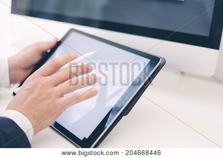Closeup view of two male hands holding electronic tablet and touching screen.Businessman working at office.Horizontal.Blurred background