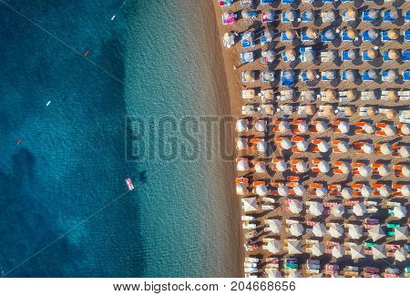Aerial view of swimming woman on the inflatable mattress in the sea . Summer seascape with girl, clear azure water and sandy beach with colorful chaise-lounges in sunny day. Top view from flying drone