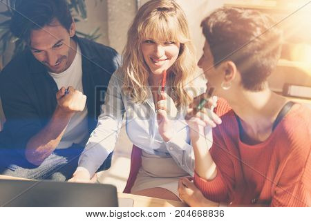 Group of happy coworkers making great conversation during work process in modern office.Business people meeting concept.Blurred background.Horizontal