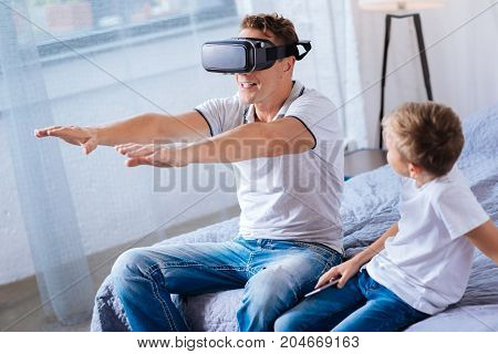 Exciting game. Pleasant pre-teen boy sitting on the bed near his father and watching him play with a VR headset, reaching out two hands