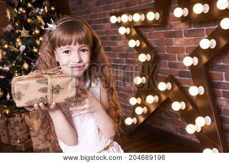 Little girl. Christmas interior. Gift and star