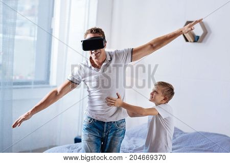Providing support. Cheerful pre-teen boy holding his father, providing him with balance, while the man playing with a VR headset and spreading hands as if flying
