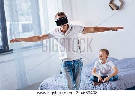 Tangible reality. Happy young man wearing a VR headset and spreading hands wide as if imitating flight while his son sitting on the bed and looking at him with smile