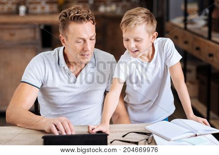 Helpful advice. Charming pre-teen boy giving his father a piece of advice regarding a tablet and pressing necessary icon on tablet while the father listening to him attentively