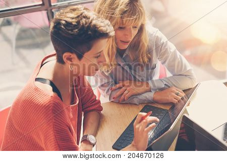 Tow beautiful business women making conversation at modern studio office .Handsome coworkers at working process.Horizontal, blurred