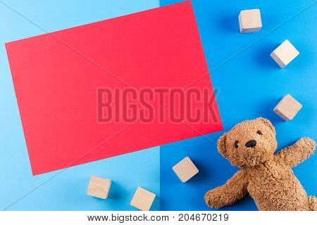 Kids toys background with teddy bear, cars and wooden blocks and blank red card for text