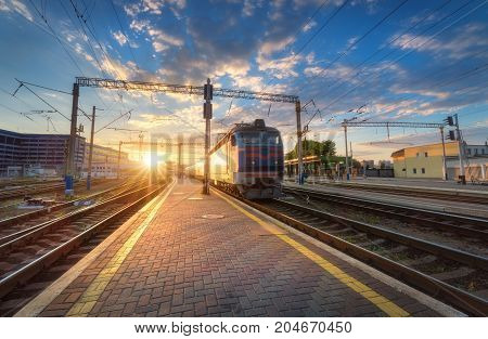 High speed passenger train on railroad track at sunset in Europe. Railway station with modern commuter train departure, blue sky with clouds and sun. Colorful Industrial landscape. Railway platform
