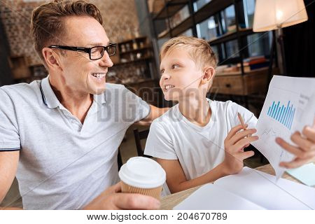 Explanation needed. Adorable pre-teen boy sitting at the table in the study next to his father and asking him about the charts depicted on the printout in his hands