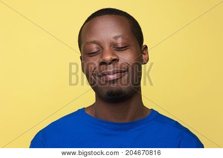 Satisfied young black man. Happy mood yellow background. Pleased African American guy, happiness concept