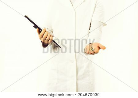 Male Hands Of Doctor Holding Clipboard And Pills
