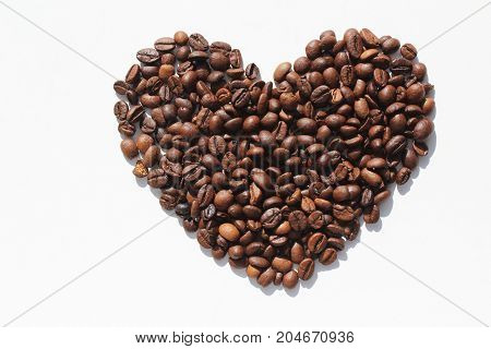 Heart of roasted coffee beans on white background