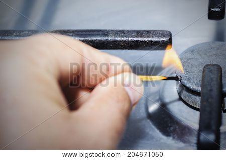 A man lighting the gas-stove with a match.
