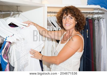a forties woman shopping in clothing store
