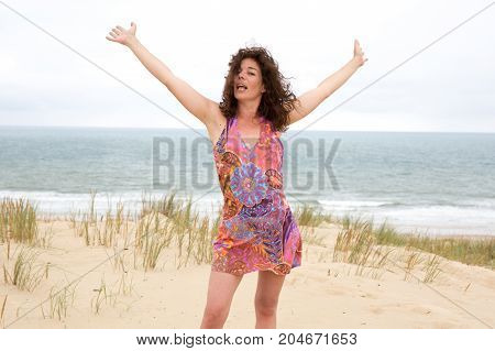 Forties Woman Standing On A Sandy Beach Arms Happy