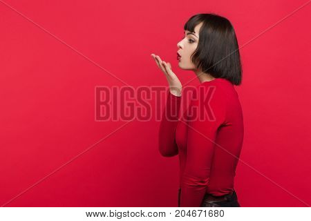 Flirty young female. Seduction background. Woman sending air-kiss, love relationship concept