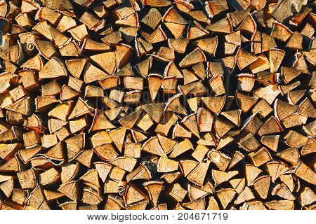 Rural style background - woodpile of chopped firewood stock up for fireplace or sauna. Close-up capture.