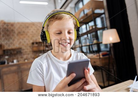 Favorite music. Pleasant upbeat boy sitting on the table in the study and listening to the music on the headphones while scrolling his phone, choosing the next song to play